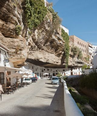 Setenil de las Bodegas, Spain  This small Spanish town along the Rio Trejo in Cadiz has a split personality: many residents in the lower half continue to live in cavelike structures built into a gorge. Large rock formations jut out over some streets, providing welcome shade during sultry summer months, and cafés make use of locally cultivated chorizo, almonds, and olives.
