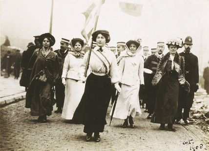 Image depicts Miss Daisy Dugdale in Suffragette uniform leading a procession to welcome Mrs Pankhurst & Christabel Pankhurst on their release from Holloway Prison