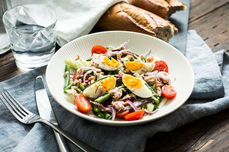 Recept voor salade Niçoise voor 4 personen. Met zout, water, olijfolie, peper, sperzieboon, tonijn uit blik, ijsbergsla, cherrytomaat, rode ui, ansjovis, ei, mayonaise, mosterd, balsamico azijn en Italiaanse bol