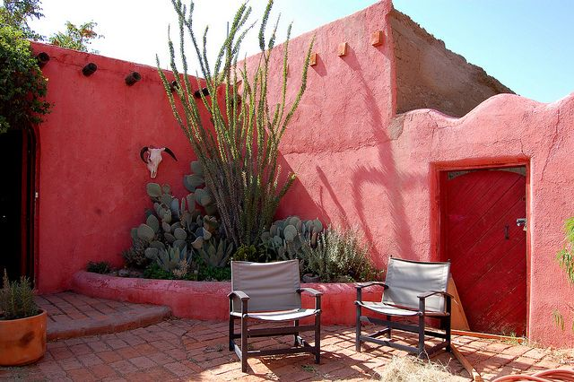 Adobe walls, cactus, brick Mexican courtyard. Warm and vivid.