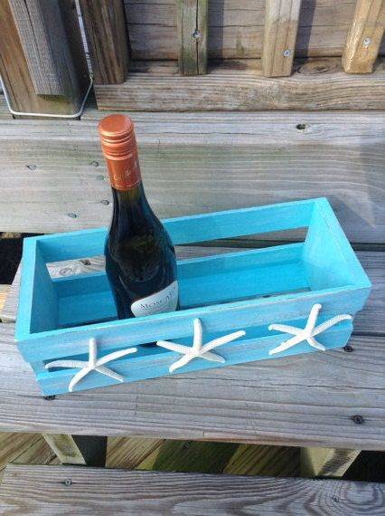 Our eye-catching starfish Crate is a great storage solution for displaying wine bottles on the kitchen counter, soaps or washcloths in the bath or holding baby supplies in the nursery. Solid wooden crate measures 15 long x 5 tall and has been hand painted and distressed. Three white finger starfish are firmly attached to the front. Available in turquoise as shown, white and cream. Other colors may be available, just send us a message!    Completion time for this item is approximately 1 week…
