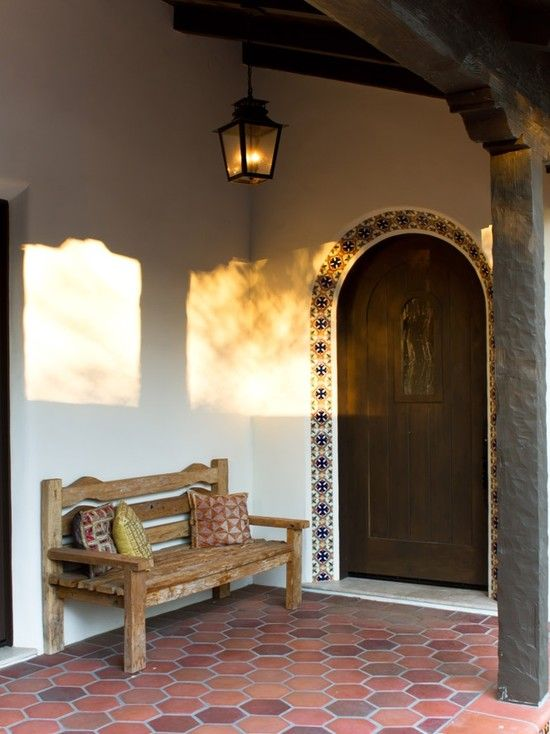 Spanish Colonial in Pasadena. Outdoor ideas: hanging lamp, tiled arch, wooden bench, and hexagonal terracotta floor