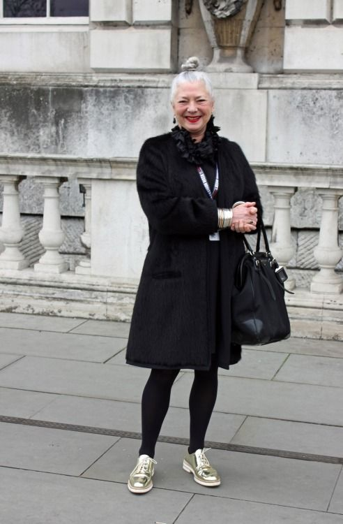 """What the grownups are wearing in London: the fabulously silver haired Professor Wendy Dagworthy, head of Fashion at the Royal College of Art, wears a black Alpaca coat designed by her friend and colleague English designer Betty Jackson, Cos dress and Betty Jackson """"ruffly thing"""" with gleaming gold brogues from Zara, Prada bag, and her signature armful of bracelets and jet earrings. Photograph by Jane de Teliga"""