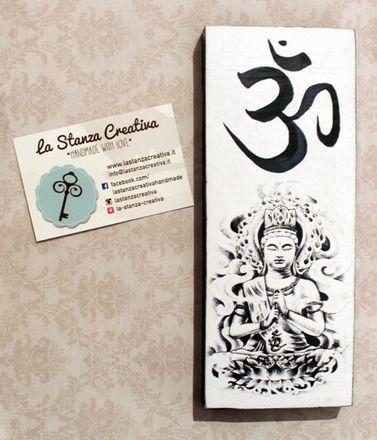Targhetta in legno con immagine di Buddha e simbolo dell'ohm, decorata interamente a mano, con bordi neri e con buco sul retro per appenderla. Dimensione del legno 8x20 cm. È po - 20332926