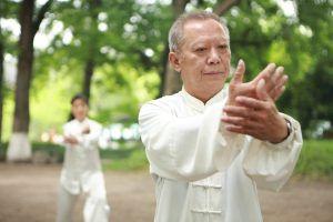 Oudere deelnemer aan Tai Chi in Japan in de buitenlucht