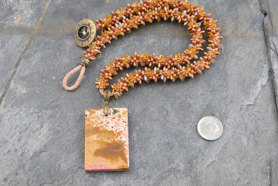 Ocean Jasper Pendant Bead Necklace with Kumihimo Bead Strand #necklace #pendant #pendantbead #pendantbeadnecklace #kumihimo #kumihimonecklace #handmade #woven #knotted #handwoven #handknotted #oneofakind #ocean #oceanjasper #oceanjasperpendant #beachy #spiky #rizo #rizobeads #seedbeads #natural #organic #stunning #honey #pink #peach #copper #boho #bohemian #japanese #weaving #japaneseweaving