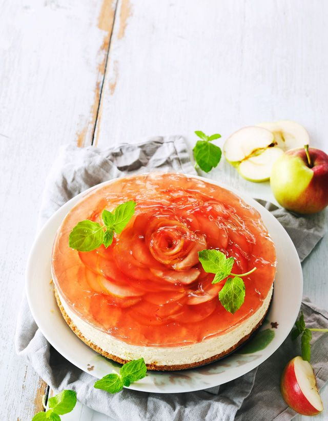 Leivo astetta fiinimpi valkosuklaajuustokakku. Asettele pintaan ruusu omenaviipaleista ja hyytelöi vaaleanpunaisella mehulla.