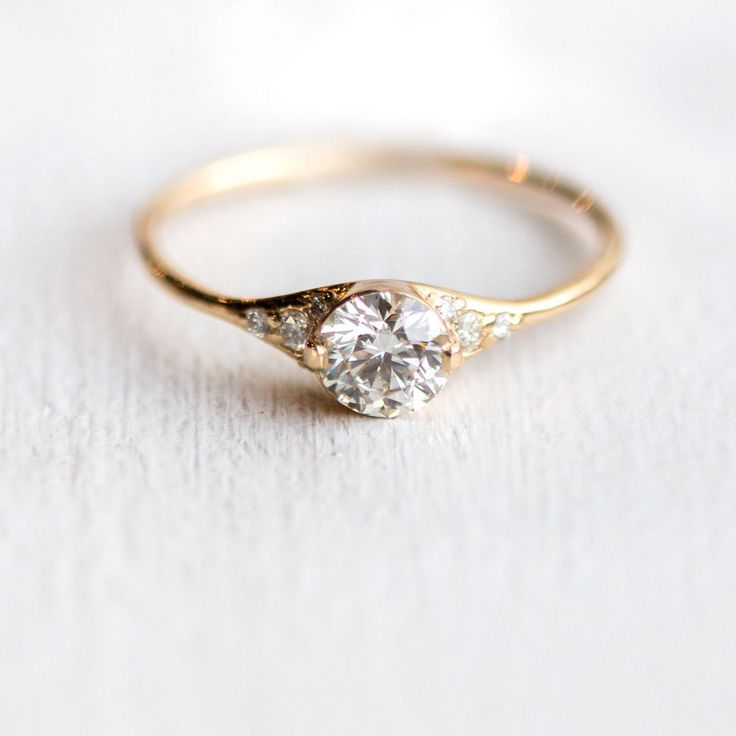 Solid 14k yellow gold engagement ring with sparkling white diamonds on both tapered sides and a 5mm round center white diamond; handmade by Melanie Casey.