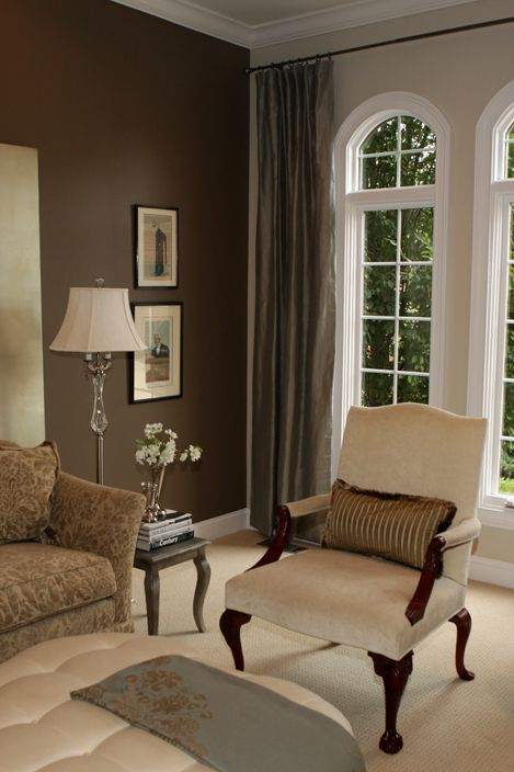 Chocolate brown accent wall with white woodwork and tall windows