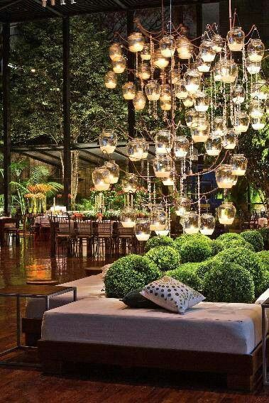 Awesome candle chandelier in lounge area of event. Also love the cluster of shrubberies in between the benches.