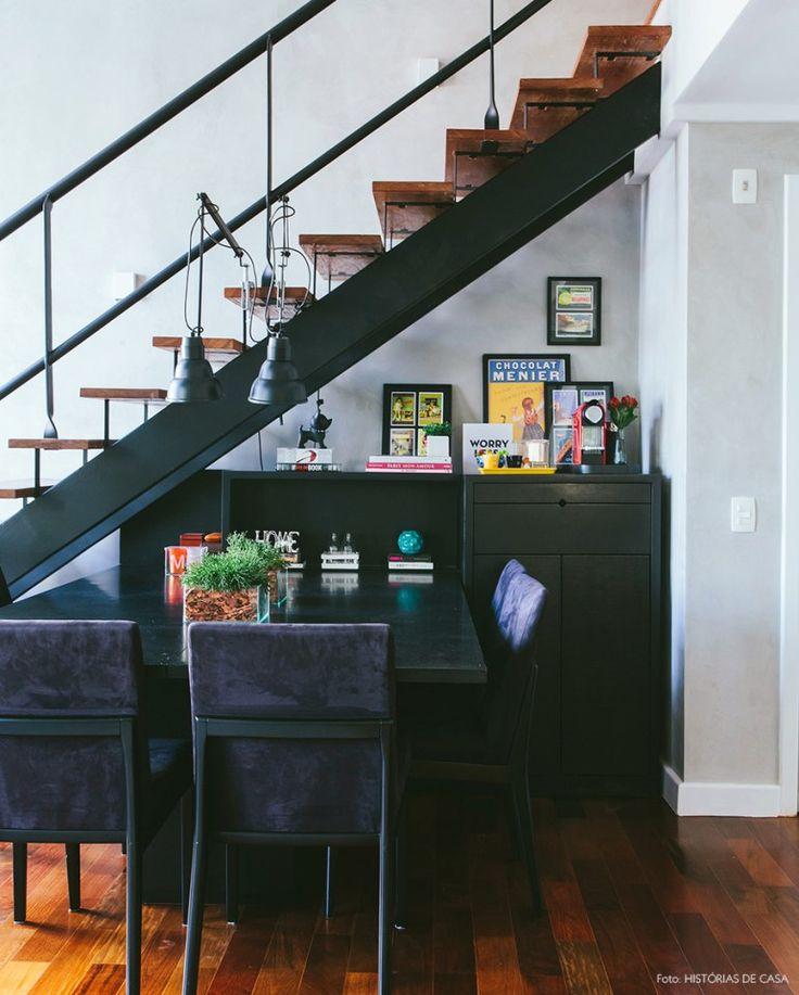 Sala de jantar com marcenaria e móveis na cor preta e pitadas de cores nos objetos de decoração.