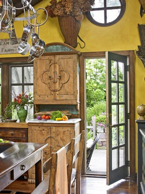 The circle window up high is great and will work at the beach house love this mustard yellow walls and rustic cupboards that give this kitchen a