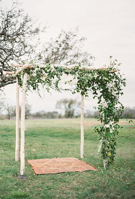 Brides.com: . An earthy and rustic chuppah with draped fabric ceiling and dark greenery.