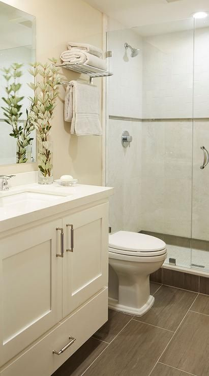 Small welcoming cream bathroom features a cream washstand placed on wood like floor tiles and fitted with a bottom drawer, satin nickel pulls, and a white quartz countertop holding a sink with a polished nickel faucet beneath a framless vanity mirror mounted to a cream wall.