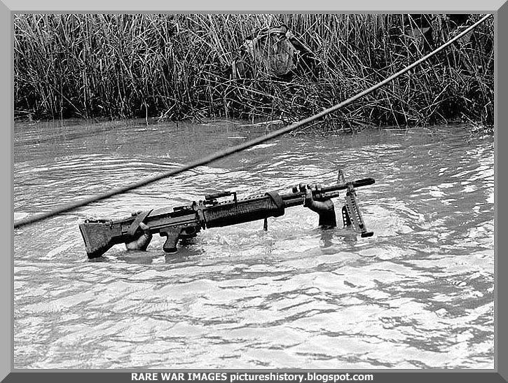 Saving his gun. Mekong Delta. 1968 ....powerful photo.  This is an American solider during the Vietnam War -