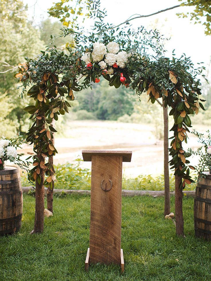 Fold lush wedding florals and greenery into a natural outdoor ceremony arch for a rustic look.