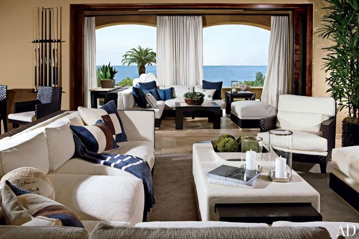 """Magic Johnson Basketball legend Earvin """"Magic"""" Johnson and his wife, Cookie, wanted a laid-back, welcoming feel for their family's seaside getaway in Southern California. Designer Michael Kreiss chose off-white sofas and blue accents for the family room and adjacent terrace to echo the sand and sea just beyond. (December 2009"""