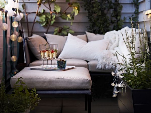 An upholstered ottoman does double-duty as seating or a coffee table on a small apartment balcony.