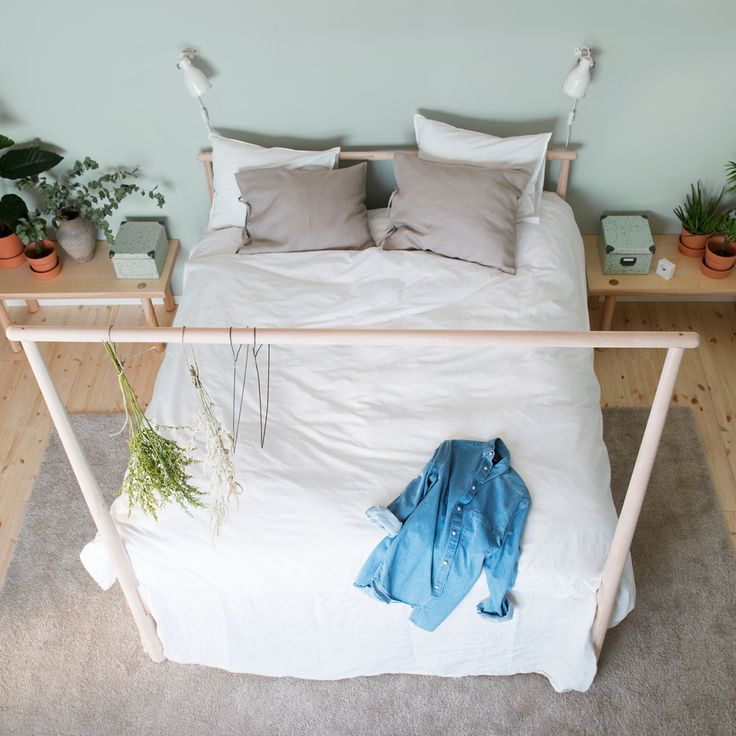 a bed with lightly colored natural textiles against a light green wall in a symmetrical bedroom with low bedside tables and touches of nature