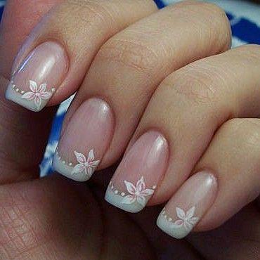 Linda manicura francesa adornadas con flores blancas en los bordes y pequeños lunares.