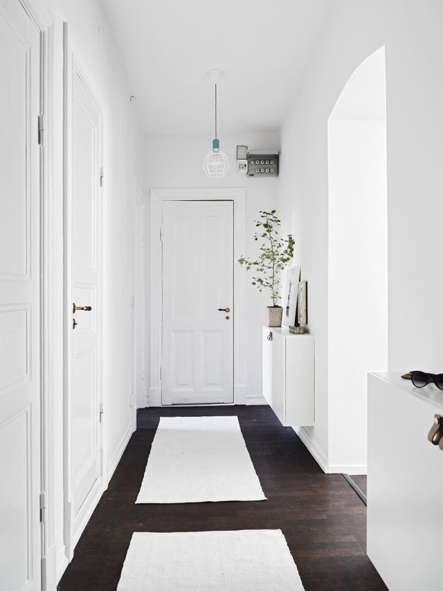 Une entrée avec des murs flancs et des tapis en coton rectangulaires et blancs