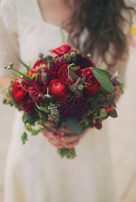 Brides.com: . Bouquet of dahlias, ranunculuses, seeded eucalyptus, sweet pea tendrils, perennial mums, snapdragons, ilex berries, and scabiosas, $225, Greenlion Design