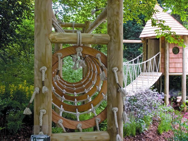 An elevated playhouse was added to this backyard design complete with a swinging bridge walkway