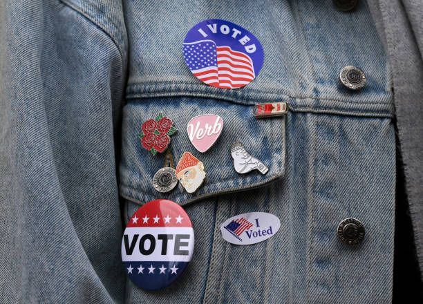 Stickers and pins are pictured on a denim jacket during the Berklee College of Music 'Get Out the Vote Initiative,' at City Hall Plaza in Boston on Nov. 7, 2017. Organizer Will Lenart said he was motivated to organize the non-partisan event by the low voter turnout in the primary. 'We want to encourage walkers-by to vote. Voting day is supposed to be a celebration, it's an important day for our city.'