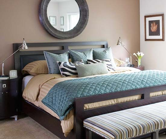 In this bedroom, a soothing palette of soft teals, blue-grays, and browns brings a feeling of serenity. Add a focal point such as the mirror above the bed to attract the eye. The warm brown walls pair with the cooler blue tones to create an inviting personal retreat.