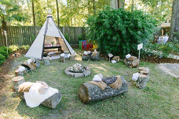 Tipi en boomstammen met schapen/koeienvellen rond het kampvuur.