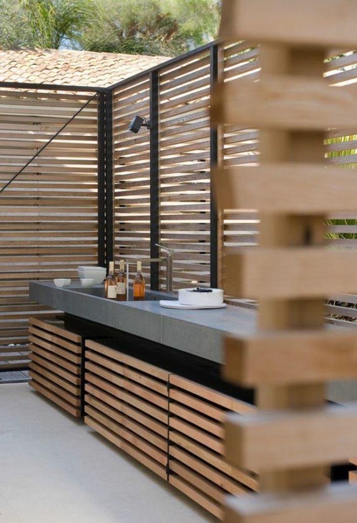 une élégante cuisine d'extérieur en béton et en bois, délimitée par une palissade