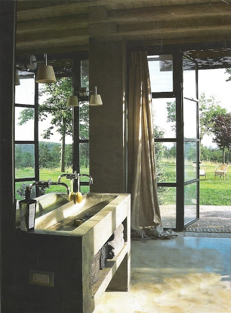 This bathroom features a trough sink and a wall of windows and doors. Fresh and open to the outdoors.