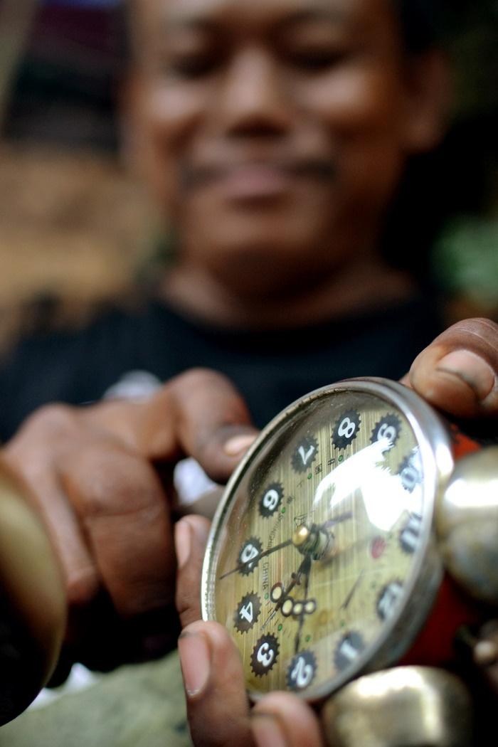 Time travel. A trader in Triwindu market repairs an antique clock. Photo by Stefanus Ajie.