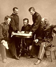Generals Wesley Merritt, Philip Sheridan, George Crook, James William Forsyth,   and George Armstrong Custer  around a table examining a document.