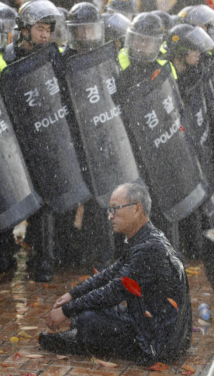 A protester sits in front of riot police as the police use water cannons to disperse a rally against the South Korea-U.S. free trade agreement (FTA) talks in Seoul November 3, 2011. [Credit : Jo Yong-Hak/Reuters]