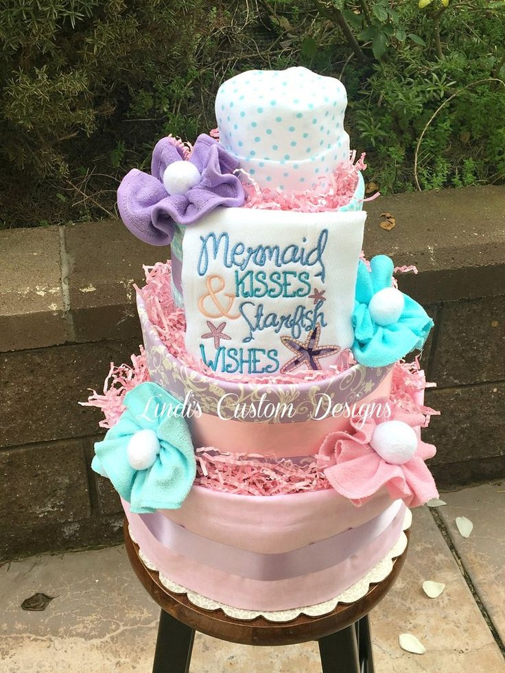 Adorable baby girl mermaid theme diaper cake is stocked with new goodies for the new or expecting mommy and baby! Our diaper cake features 4 tiers and is loaded with burp cloths, baby socks, baby wash