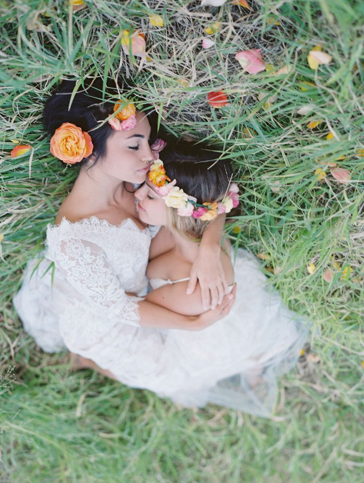 two brides with flower crowns hugging on grass