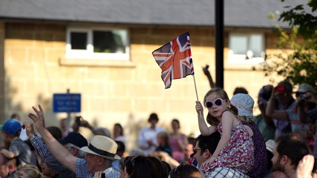 A young spectator with a Union Jack flag watches the Olympic flame travel into Bath.