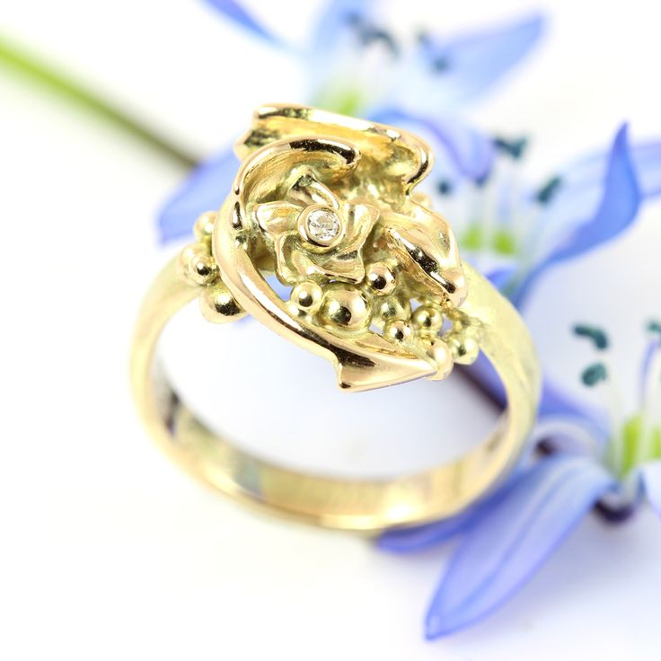 Golden dragon ring with flower. This tiny Dragonling made of 14k gold has found a treasure: golden pebbles and a flower with a diamond! Now it's cradling the riches, while protecting its wearer too.