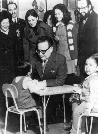 Salvador Allende inclinado conversa con niño