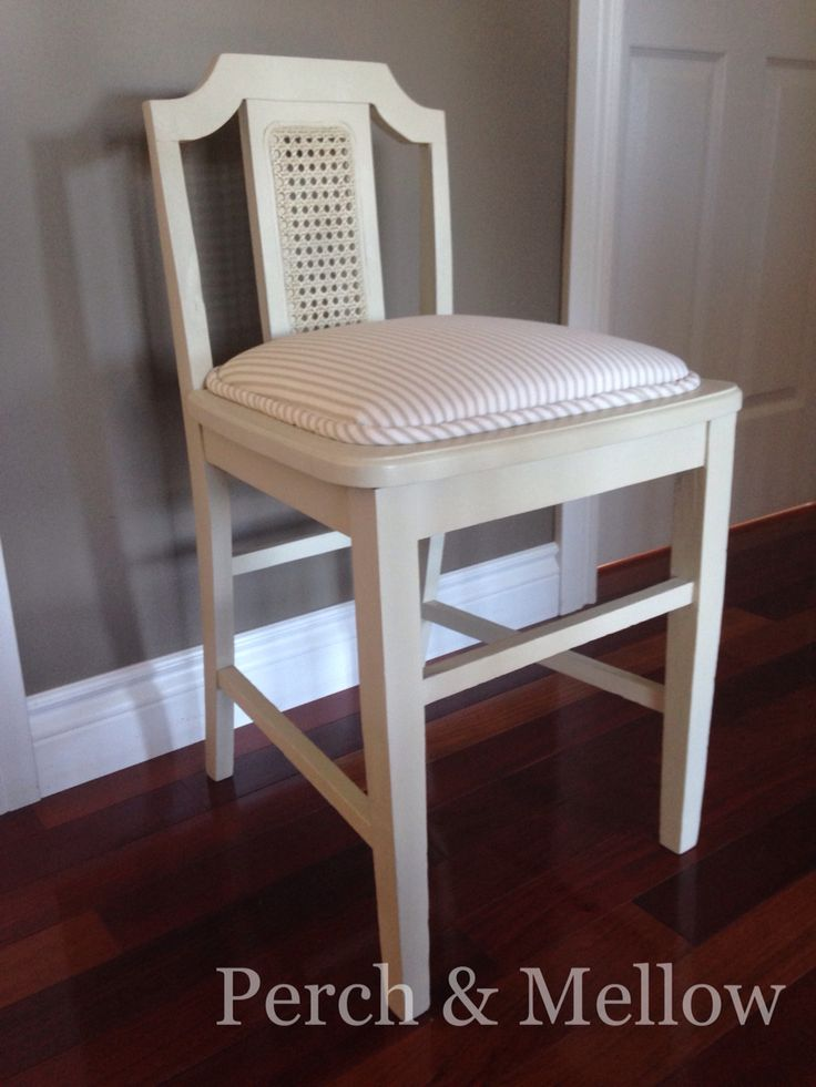 Milliner's chair restored. Ticking stripe fabric an sold ochre chalk paint. The back is low to allow ladies to try on huge hats!