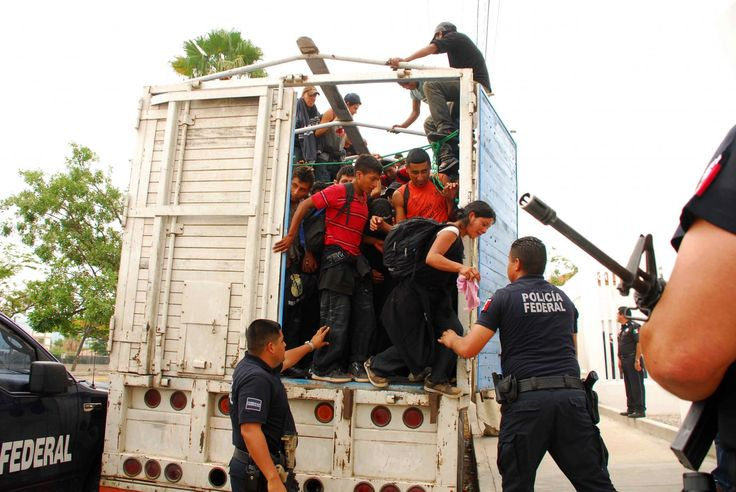 Migrants jump out of a tractor trailer as Mexican federal police watch at police headquarters in Tuxtla Gutierrez, Mexico, Sunday June 12, 2011.