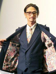 窪塚洋介は写真撮影でスーツのジャケットの派手な裏生地を見せる