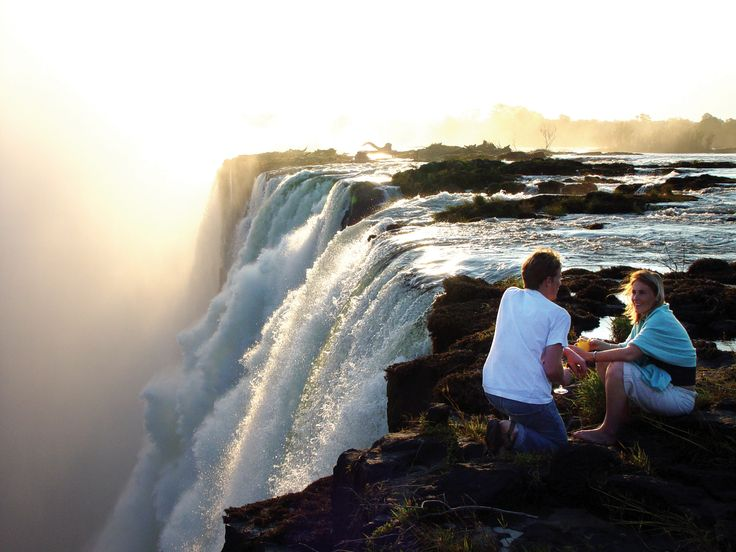 Sundowners at the edge of Victoria Falls as gallons of water from the Zambezi River cascade over The Falls every second, is an awesome experience. The spray is so high during the rainy season that The Falls is criss-crossed with a multitude of rainbows. Special places exude a powerful ambiance. Tongabezi Lodge take guests to Livingstone Island at the very edge of Victoria Falls in Zambia.