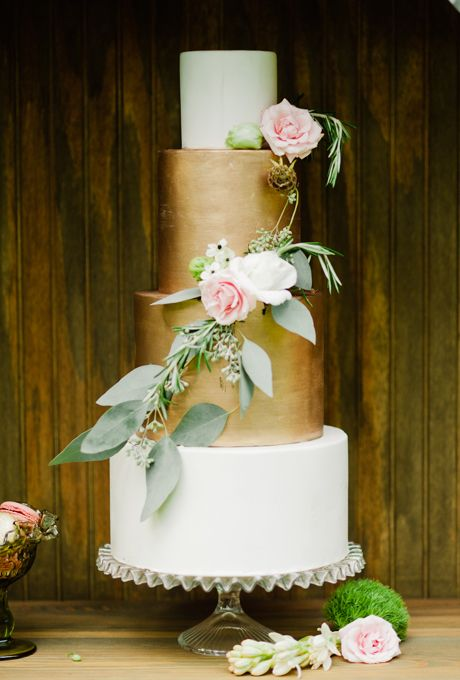 Brides.com: 29 Glam Metallic Wedding Cakes. A four-tiered wedding cake with two gold tiers and draped flower details, from Earth and Sugar.