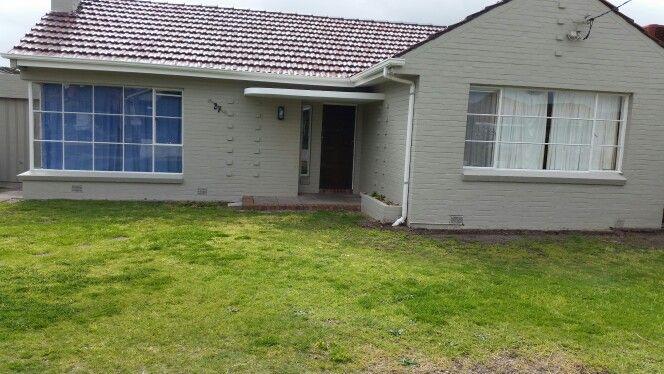 Painted grey brick house,  white window trim