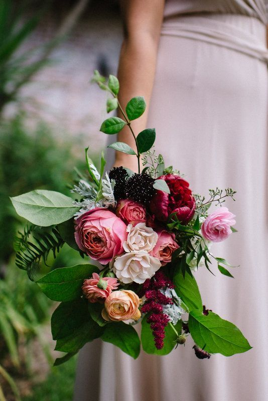 loosely tied and wild summer bridesmaid bouquet of red charm peony, pink romantic antique garden rose, pink ranunculus, white majolica spray rose, burgundy astilbe, burgundy scabiosa, dusty miller, jasmine vine, seeded eucalyptus, lemon leaf and fern.
