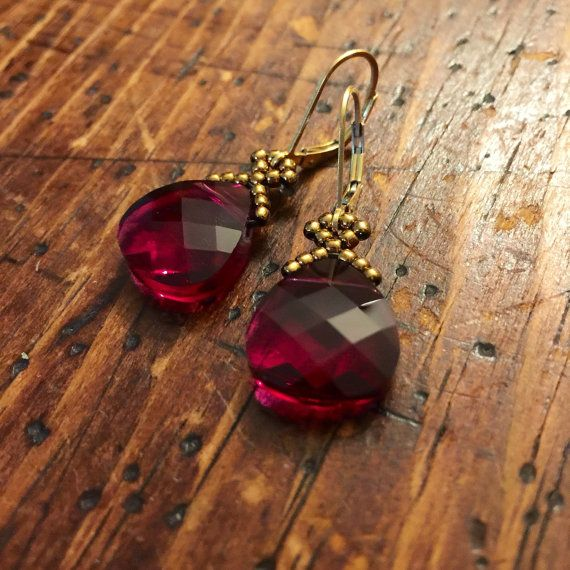 These charming Swarovski marsala red crystal earrings feature a 14x15mm ruby red flat briolette, beadwoven with antique gold glass seed beads, and finished with gold plated leverbacks. The length of the earrings from the top of the earwire to the bottom of the crystal teardrop is approximately 1 3/8 inches, 35mm. These shimmery garnet crystal earrings are super versatile! Wear them for a wedding or another special occasion, or with your favorite sweater and jeans as a funky statement loo...