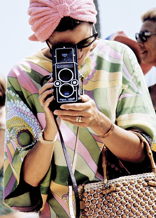 Grace Kelly taking a photograph at a swimming competition at Palm Beach, Monte Carlo, 1972.