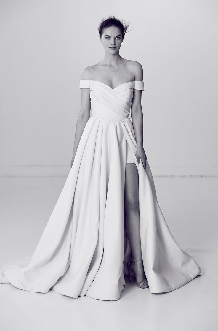 """Alyne by Rita Vinieris's """"Brilliant"""" dress from the spring 2018 collection is an off-the-shoulder floor-length gown with a draped bodice ballgown, and multi-pleated skirt detailed with a high leg slit."""